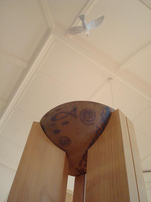 Foto på dopfunten i kyrkan. Ovanför dopfunten hänger en duva i taket.